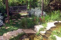 גינה יפה ללא דשא - ספסל צופה לבריכת נוי בגינה